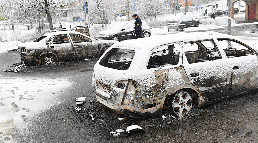 A policeman investigates a burnt car in Rinkeby, Sweden February 21, 2017. Click to enlarge