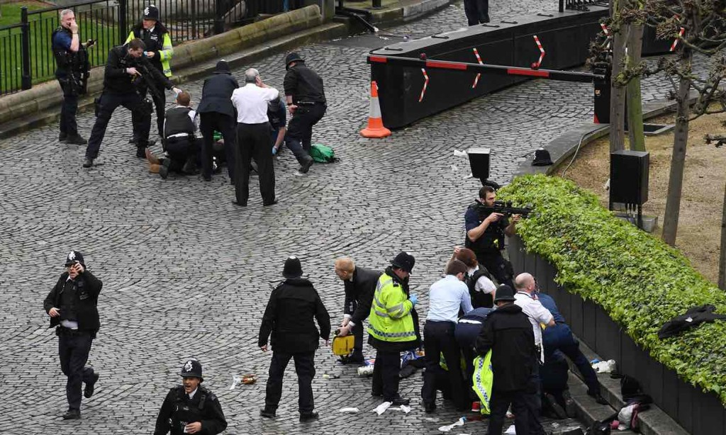 A policeman points a gun at a man on the ground as emergency services attend the scene outside the Palace of Westminster, London. Click to enlarge