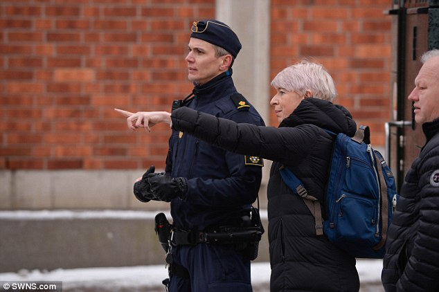Katie speaks to a policeman after a grenade was found in a bin outside the Kista Police Station. Click to enlarge