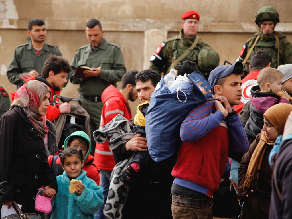 Syrian Army and Russian soldiers monitor as rebel fighters and their families evacuate Homs last week. Click to enlarge