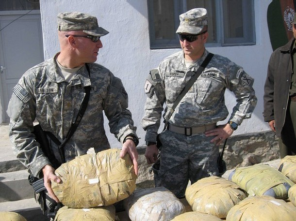 U.S. soldiers inspect a cache of opium that was seized at a border police station on the outskirts of Herat, 23 October 2007. Afghan border police in the western Afghan city have seized 644 kilograms of opium. Afghanistan accounts for over 93 percent of the world's supply of opium, the main ingredient in heroin, a lucrative trade whose proceeds in part fund some of the Taliban-led insurgency.    AFP PHOTO/STR (Photo credit should read STR/AFP/Getty Images)