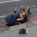 "A woman assists an injured person after an incident on Westminster Bridge in London, Britain March 22, 2017.  REUTERS/Toby Melville    SEARCH ""MELVILLE WESTMINSTER"" FOR THIS STORY. SEARCH ""WIDER IMAGE"" FOR ALL STORIES.  TPX IMAGES OF THE DAY - RTX329ML"
