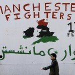 "Two men walk past graffiti painted on a wall in Tripoli that pays homage to the so-called ""Manchester Fighters"", in reference to a group of British-born Libyans who joined the rebel fighting against late Libyan leader Gaddafi. Click to enlarge"