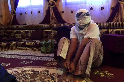 A former detainee shows how he was kept in handcuffs and leg shackles while held in a secret prison at Riyan airport in the Yemeni city of Mukalla in this May 11, 2017 photo. He covered his face for fear of being detained again. He and other former detainees say abuses are widespread in a network of secret prisons run by the United Arab Emirates and its Yemeni allies, into which hundreds detained in the hunt for al-Qaida militants have disappeared. (AP Photo/Maad El Zikry). Click to enlarge