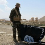 A member of Syrian pro-government forces carries an Isis flag in Palmyra in March 2016. Click to enlarge