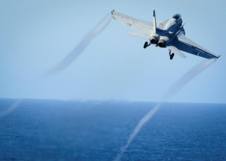 An F/A-18E Super Hornet takes off from the flight deck of a U.S. Navy aircraft carrier. Click to enlarge