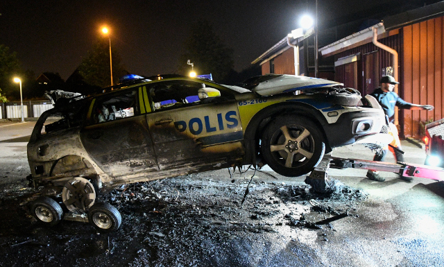 Burnt out police car in Malmö, Sweden, 2016. Click to enlarge