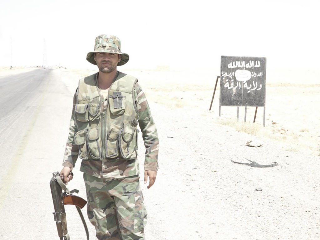 A Syrian soldeir in front of a sign on the main road to Homs comma dash welcoming undash visitors to the dash Isis Caliphate Province of Raqqa