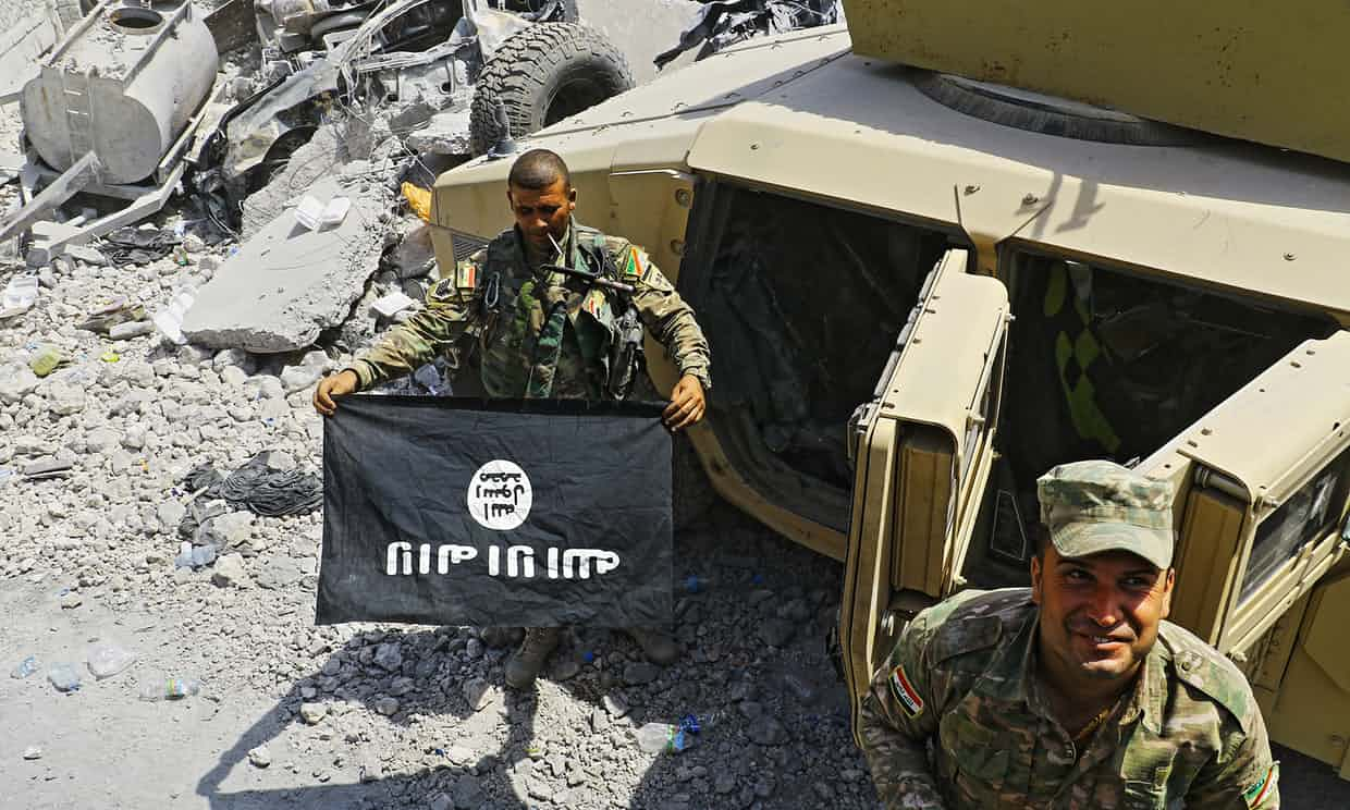 Iraqi soldier holds ISIS flag in the rubble of Mosul. Click to enlarge