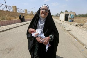 An elderly displaced Iraqi woman carries a baby in Mosul. Click to enlarge