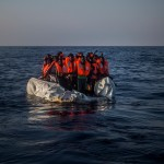 Migrants wait aboard a partially punctured rubber boat during a rescue operation off the coast of Libya. Click to enlarge