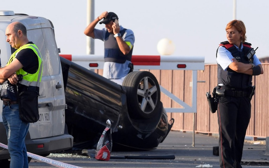 Police officers by upturned car used to target civilians in the second terror attack in Cambrils Spain
