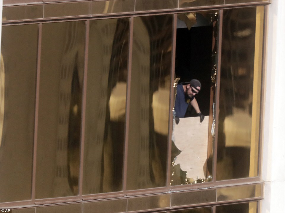 An investigator looks through one of the windows Stpehen Paddock fired from. Click to enlarge