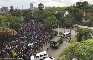 People attempt to inch their way forward on the road to State House in Harare, Saturday, Nov. 18 2017. Earlier euphoric crowds of several thousand people gathered in Zimbabwe's capital to demand the departure of President Robert Mugabe after nearly four decades in power. (AP Photo/Ben Curtis)