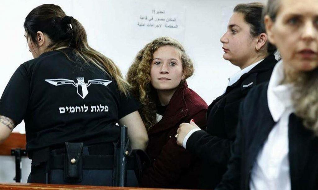 Ahed Tamimi, looking toward camera, in an Israeli court. Click to enlarge