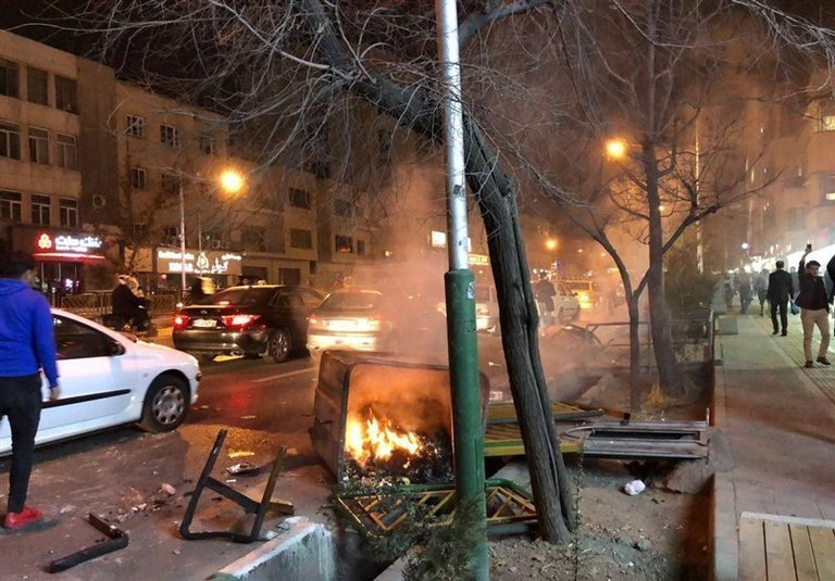 """A photo of a burning rubbish bin and a man, far right, holding a glass or bottle in the air, which the New York Times captioned: """"Unrest in the streets of Tehran on December 30, 2017"""". Click to enlarge"""