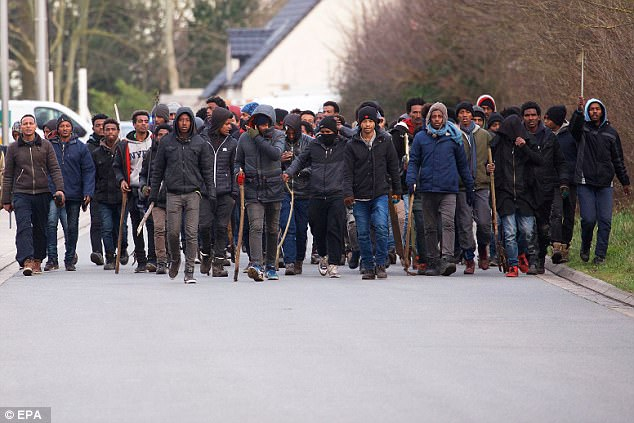 Migrants armed with sticks and rocks during clashes between rival gangs in Calais, France. Click to enlarge