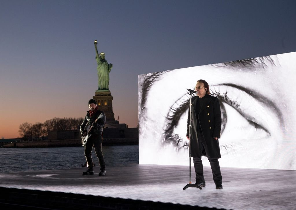 The performance took place in front of the Statue of Liberty as eyes appeared around the band. Click to enlarge