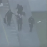 (Helicopter captured four cops emerging from school with heavy bag containing body armor.)