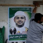 A man hangs a poster depicting Palestinian electrical engineer Fadi al-Batash, who was shot to death in Malaysia, on his family house in the northern Gaza Strip April 21, 2018. Click to enlarge