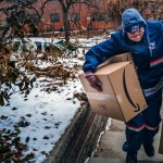 US Postal Service worker delivers Amazon packages. Click to enlarge