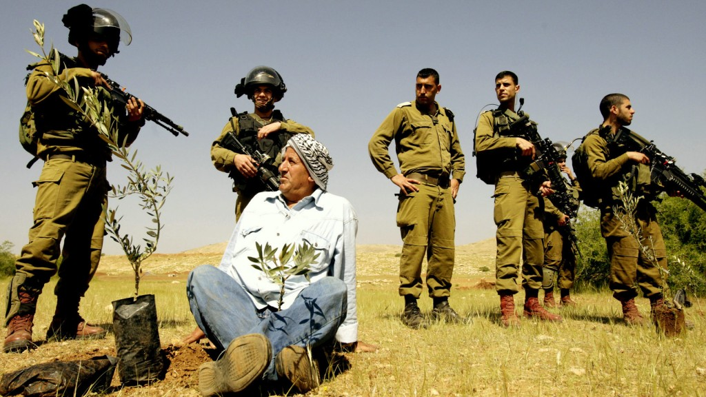 A Palestinian farmer looks at Israeli army soldiers after he planted an olive trees near the West Bank town of Tubas in the Jordan valley, during a protest against the closure of land to Palestinians by the army and Jewish settlers, Tuesday, April 8, 2014. Dozens of Palestinians protested in the Jordan valley where Palestinian sources said that Israel has closed land for the army to use for the military training. (AP Photo/Mohammed Ballas)