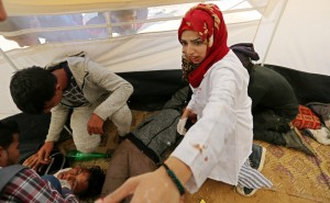 A photo taken on 1 April shows Palestinian medic Razan al-Najjar treating injured persons at an emergency medical tent during protests in Gaza near the boundary with Israel. Al-Najjar was fatally shot by an Israeli sniper as she was helping injured protesters near Khan Younis on 1 June. Ashraf Amra APA images. Click to enlarge