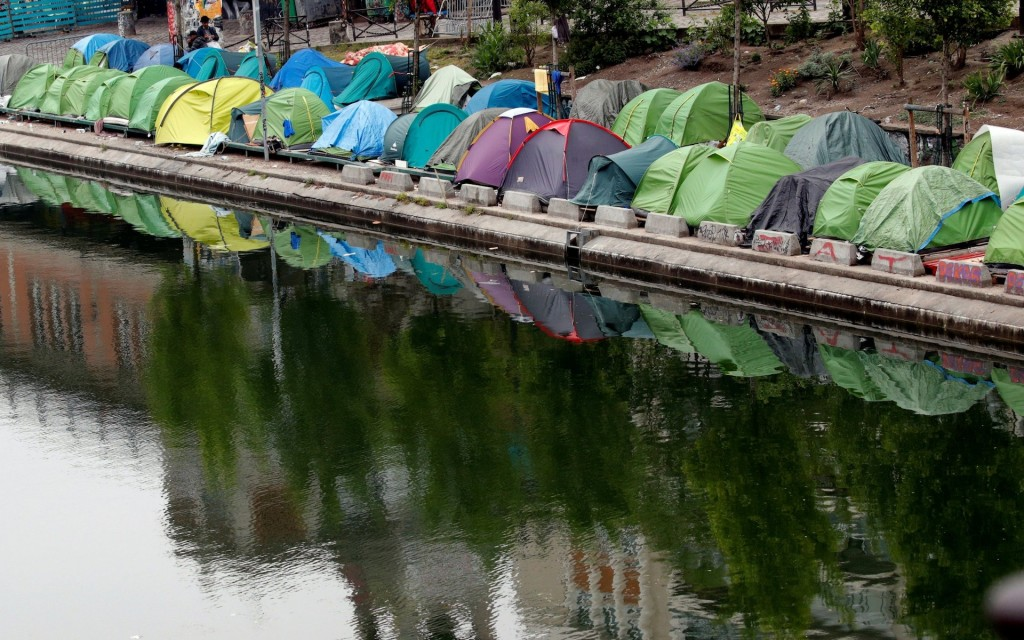 Tents in which migrants live are seen in a makeshift camp along the Quai de Valmy of the canal Saint-Martin in St Denis. Click to enlarge