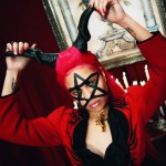This girl wears a pentagram on her face and horns on her head + a ritualistic red dress. In occult symbolism, holding horns means drawing occult power from demonic forces. Click to enlarge
