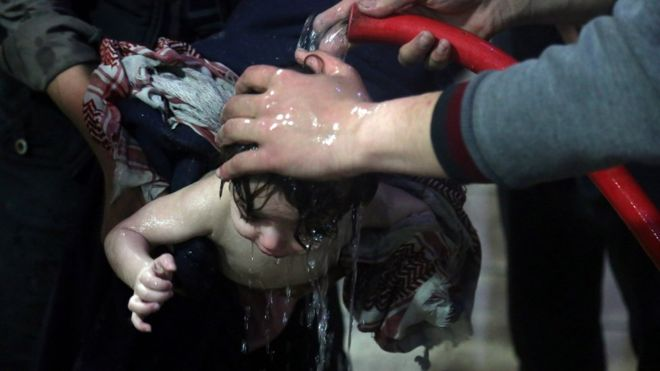 "White Helmets ""rescue workers"" wash down a purported victim of a Syrian government chemical weapons attack in Douma. This photo accompanied the BBC report on the findings of the OPCW investigation into the Douma 'attack'. Click to enlarge"