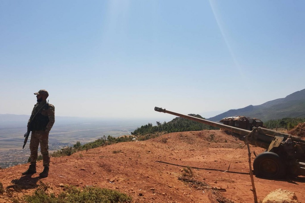 Syrian soldier stands guard over a Russian-made 130mm gun on the heights of Mount Akrad, northern Syria. Click to enlarge