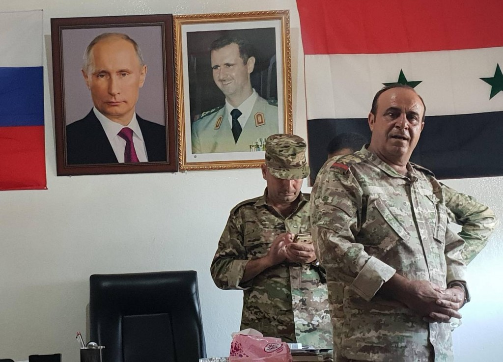 Beneath photos of Putin and Assad, General Jihad Sultan (foreground). Click to enlarge
