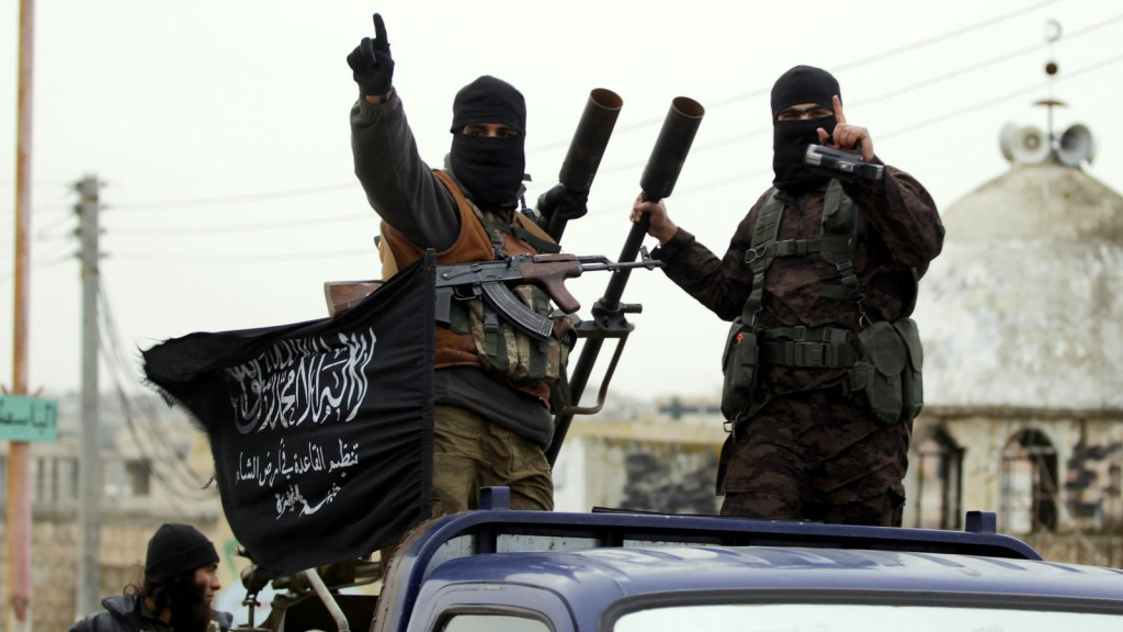 Members of the al Qaeda affiliated al-Nusra Front gesture as they drive in a convoy touring villages in the southern countryside of Syria's Idlib province, December, 2014. Click to enlarge