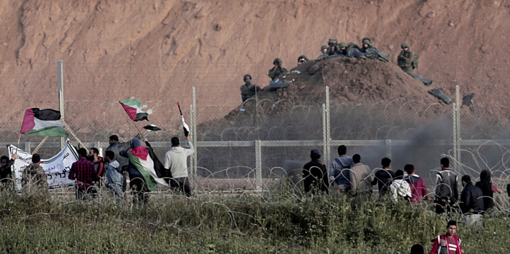 Protesters wave Palestinians flags in front of Israeli solders on Gaza's border with Israel, east of Beit Lahiya, Gaza Strip, Wednesday, April 4, 2018. A leading Israel human rights group urged Israeli forces in a rare step Wednesday to disobey open-fire orders unless Gaza protesters pose an imminent threat to soldiers' lives. (AP Photo/Adel Hana)