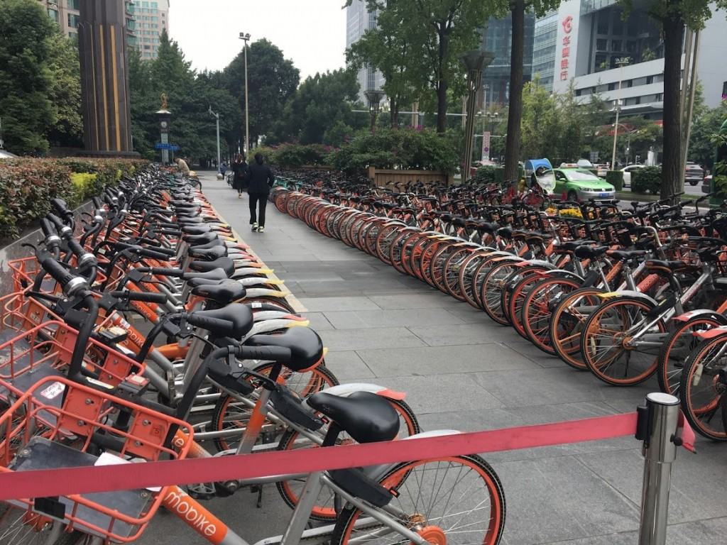 Bicycle deposits like this one are everywhere. Each ride has an electronic gizz which that lets you rent it using–what else?–WeChat. The system is not robustly communistlc: Different companies paint their bikes in different colors, and have sales to compete. Phredfoto. Click to enlarge