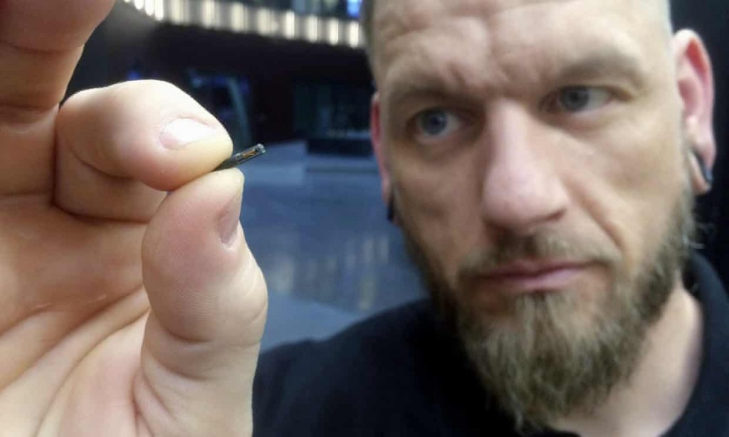 Jowan Österlund from Biohax holds a microchip implant the size of a grain of rice between his thumb and forefinger. Click to enlarge