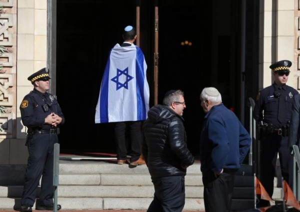 Police stand at the entrance to Rodef Shalom Temple before funeral services for brothers Cecil and David Rosenthal, victims of the Tree of Life Synagogue shooting, in Pittsburgh. Click to enlarge