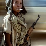 A child soldier poses with a libyan helmet, a cigarette and a Soviet-made AK-47 Kalashnikov on April 05, 1987 in Kalait (16th parallel), after the defeat of Lybian army during the Chadian-Libyan conflict. (Photo credit should read DOMINIQUE FAGET/AFP/Getty Images)