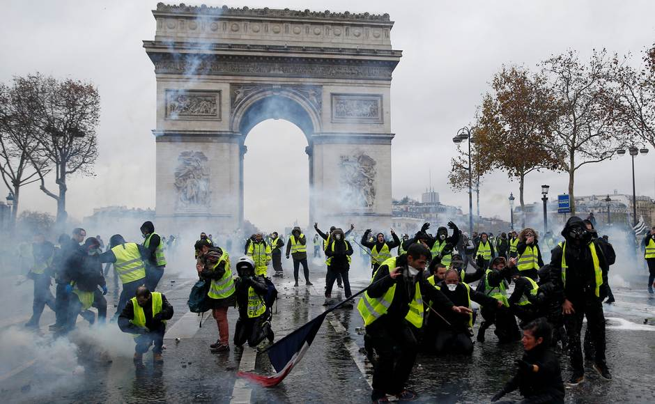 Protesters wearing yellow vests, a symbol of a French drivers' protest against higher diesel taxes, face off with French riot police during clashes at the Place de l'Etoile near the Arc de Triomphe in Paris, France, December 1, 2018. REUTERS/Stephane Mahe - RC1C62B3D170