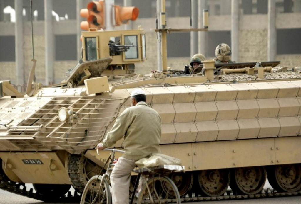 A man rides his bicycle past a British armoured vehicle near the site of a roadside bombing in Basra in February 2007. click to enlarge