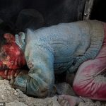 Little girl lies covered in blood under rubble after latest bombardment by Assad's regime