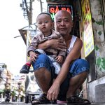 Presidential candidate Linh Dinh holding a baby. Click to enlarge