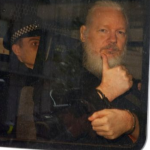 Assange gives Masonic sign of recognition while in custody of cop with Masonic checkered headband. Click to enlarge)
