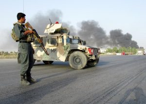An Afghan police officer keeps watch near the site of a suicide car bomb blast in Kandahar, Afghanistan July 18, 2019. Click to enlarge