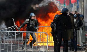 French police deal with a fire on the Champs Elysees after the Bastille Day parade. Click to enlarge