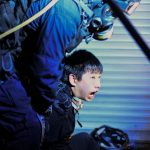 A demonstrater is held by police outside the Tsim Sha Tsui police station during protests. Click to enlarge