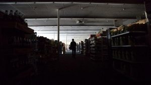 An employee walks through a darkened pharmacy during a power cut in downtown Sonoma, California, Oct 9, 2019. Click to enlarge