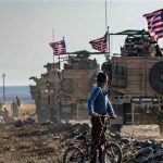A Syrian boy on his bicycle looks at a convoy of US armored vehicles patrolling fields near the northeastern town of Qahtaniyah at the border with Turkey, on October 31, 2019. (By AFP) Click to enlarge