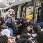 Migrants clamber aboard buses in Istanbul's Vatan Street. Click to enlarge