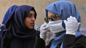 A Yemeni woman puts on a protective face mask in Yemen's capital Sana'a. Click to enlarge